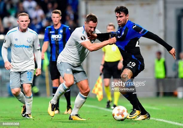 Everton's British defender Phil Jagielka vies with Atalanta's Italian forward Andrea Petagna during the UEFA Europa League Group E football match...