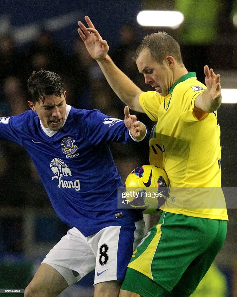 """Everton's Bryan Oviedo (L) tackles Norwich City's Steven Whittaker during the English Premiership League football match between Everton FC and Norwich City FC at the Goodison Park stadium in Liverpool, north west England on November 24, 2012. The match ended in a 1-1 draw. USE. No use with unauthorized audio, video, data, fixture lists, club/league logos or """"live"""" services. Online in-match use limited to 45 images, no video emulation. No use in betting, games or single club/league/player publications."""