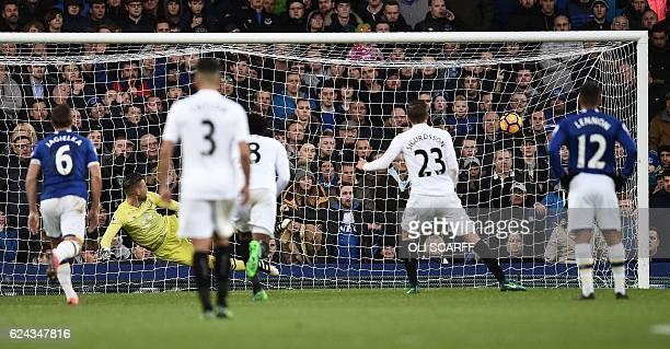 Everton's Dutch goalkeeper Maarten Stekelenburg looks to the ball as Swansea City's Icelandic midfielder Gylfi Sigurdsson scores his team's first...
