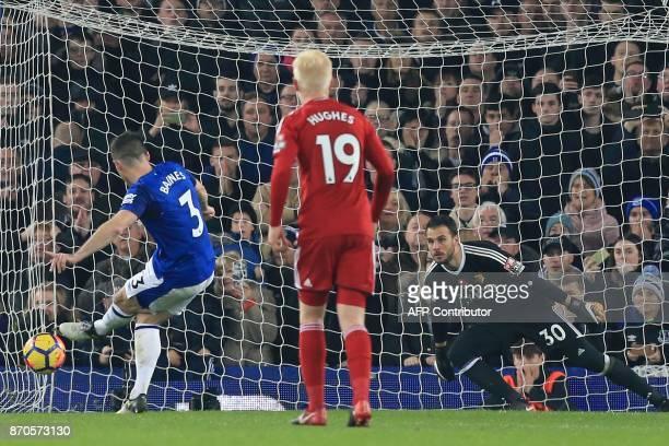 Everton's English defender Leighton Baines scores their third goal from the penalty spot past substitute goalkeeper Orestis Karnezis during the...