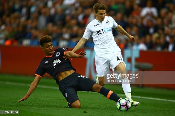 Everton's English defender Mason Holgate slides in to try to tackle Swansea City's English midfielder Tom Carroll during the English Premier League...