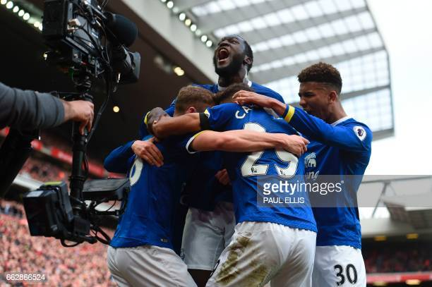 Everton's English defender Matthew Pennington celebrates with Everton's Belgian striker Romelu Lukaku and teammates after scoring their first goal...