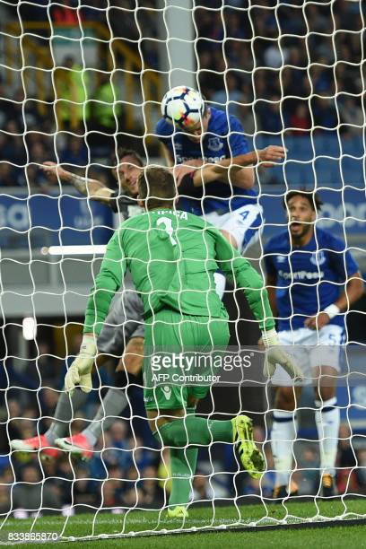 Everton's English defender Michael Keane heads the opening goal past Hajduk Split's Croatian goalkeeper Dante Stipica during the UEFA Europa League...