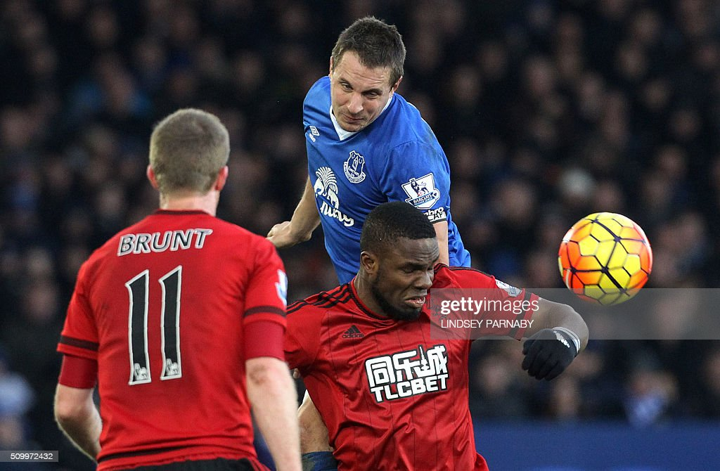 Everton's English defender Phil Jagielka (C) vies with West Bromwich Albion's Nigerian striker Victor Anichebe (R) during the English Premier League football match between Everton and West Bromwich Albion at Goodison Park in Liverpool, north west England on February 13, 2016. / AFP / LINDSEY PARNABY / RESTRICTED TO EDITORIAL USE. No use with unauthorized audio, video, data, fixture lists, club/league logos or 'live' services. Online in-match use limited to 75 images, no video emulation. No use in betting, games or single club/league/player publications. /
