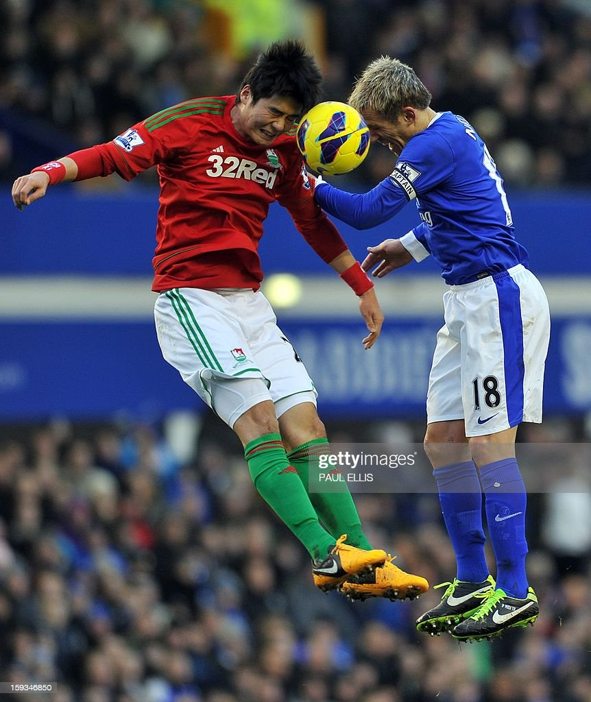 """Everton's English defender Phil Neville (R) is challenged by Swansea City's South Korean midfielder Ki Sung-Yueng during the English Premier League football match between Everton and Swansea City at Goodison Park in Liverpool on January 12, 2013. AFP PHOTO/Paul ELLIS- RESTRICTED TO EDITORIAL USE. No use with unauthorized audio, video, data, fixture lists, club/league logos or """"live"""" services. Online in-match use limited to 45 images, no video emulation. No use in betting, games or single club/league/player publications."""