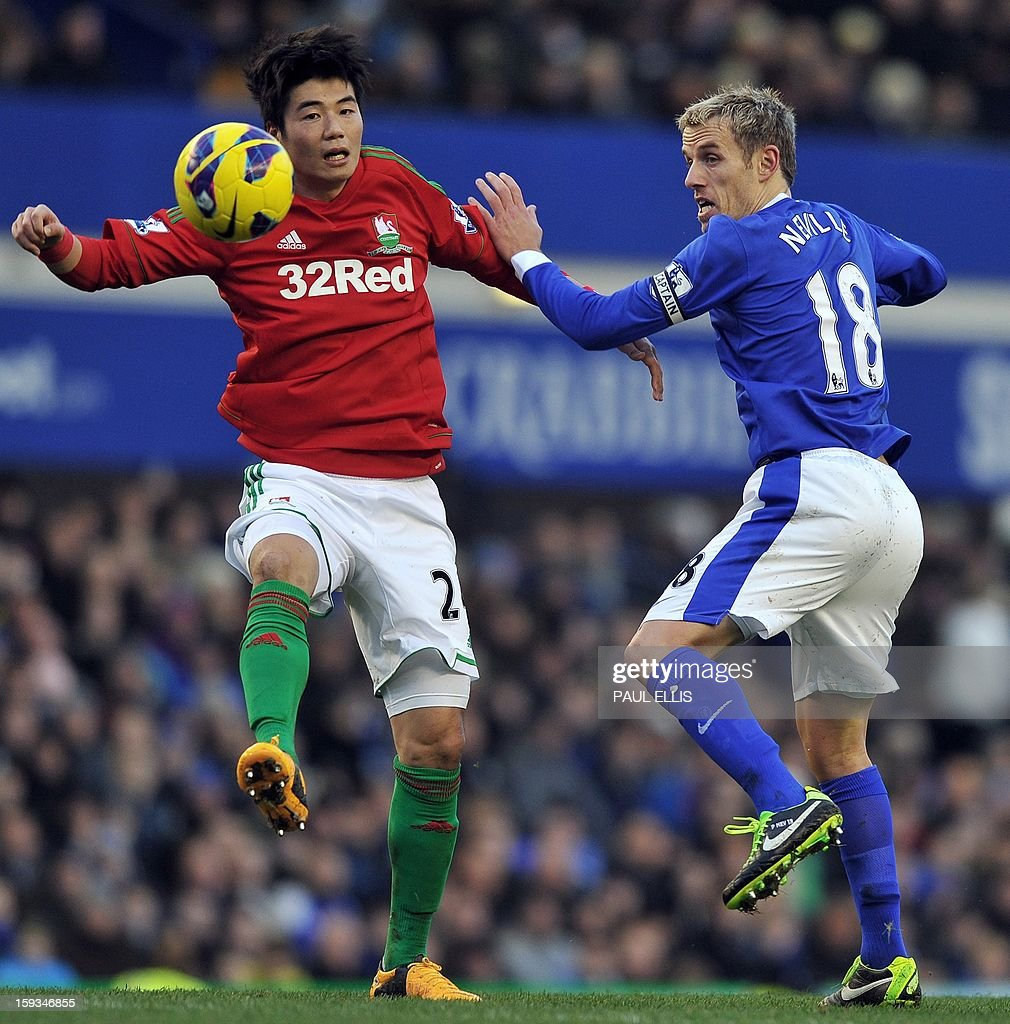 "Everton's English defender Phil Neville (R) is challenged by Swansea City's South Korean midfielder Ki Sung-Yueng during the English Premier League football match between Everton and Swansea City at Goodison Park in Liverpool on January 12, 2013. AFP PHOTO/Paul ELLIS- RESTRICTED TO EDITORIAL USE. No use with unauthorized audio, video, data, fixture lists, club/league logos or ""live"" services. Online in-match use limited to 45 images, no video emulation. No use in betting, games or single club/league/player publications."