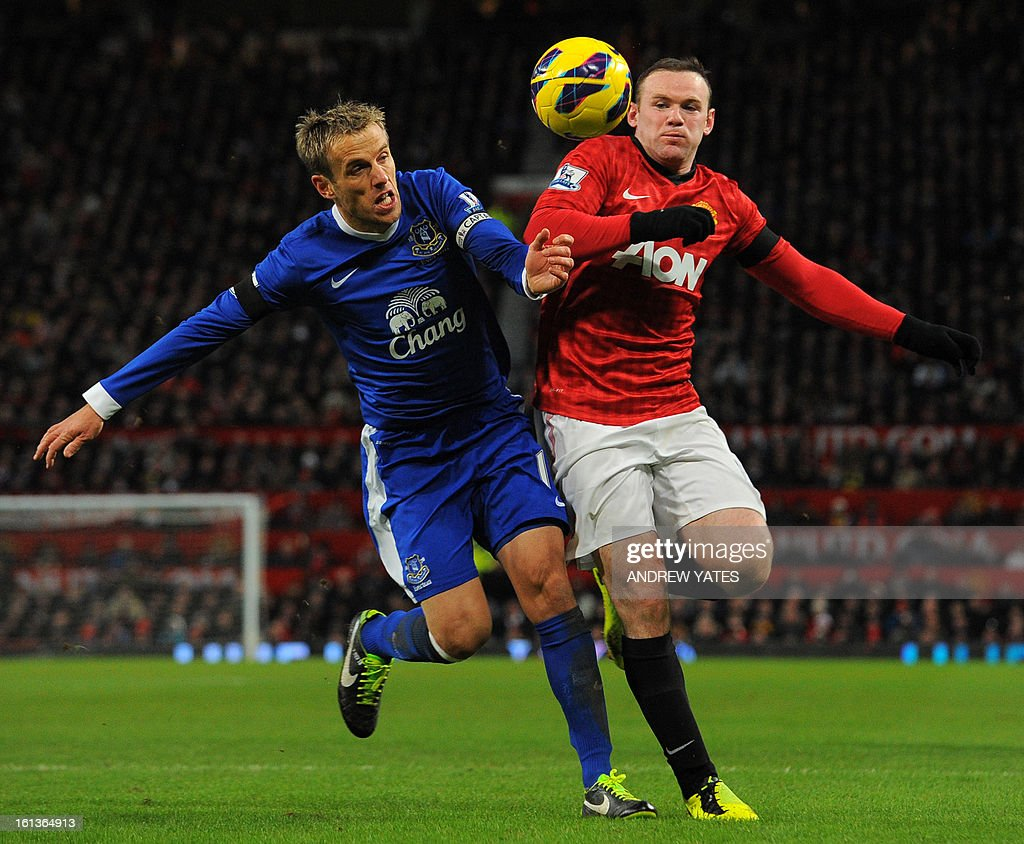 """Everton's English defender Phil Neville (L) tangles with Manchester United's English striker Wayne Rooney (R) during the English Premier League football match between Manchester United and Everton at Old Trafford, Manchester, North West England, on February 10, 2013. USE. No use with unauthorized audio, video, data, fixture lists, club/league logos or """"live"""" services. Online in-match use limited to 45 images, no video emulation. No use in betting, games or single club/league/player publications."""