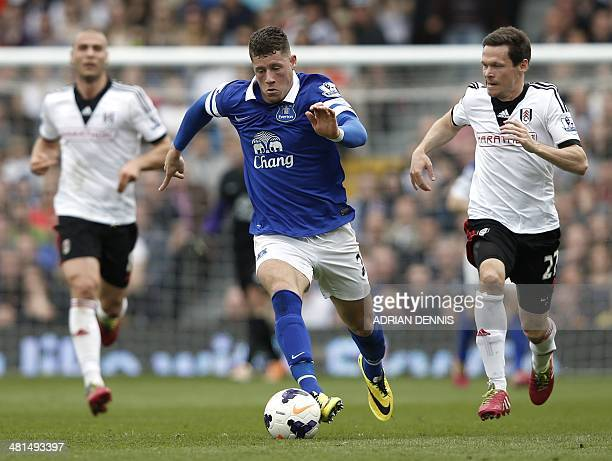 Everton's English midfielder Ross Barkley dribbles the ball chased by Fulham's German defender Sascha Riether during the English Premier League...