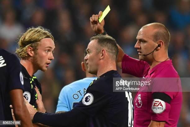 Everton's English midfielder Tom Davies is booked by referee Robert Madley as Everton's English striker Wayne Rooney intervenes during the English...