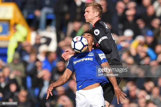 Everton's English striker Dominic CalvertLewin challenges Arsenal's German defender Per Mertesacker for the ball during the English Premier League...