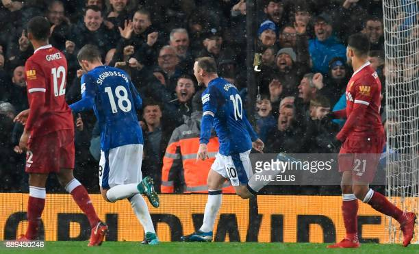 Everton's English striker Wayne Rooney celebrates after scoring an equalising goal from the penalty spot to make the score 11 during the English...