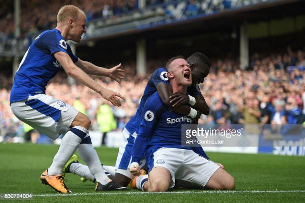 Everton's English striker Wayne Rooney celebrates scoring the opening goal with Everton's Dutch midfielder Davy Klaassen and Everton's Senegalese...