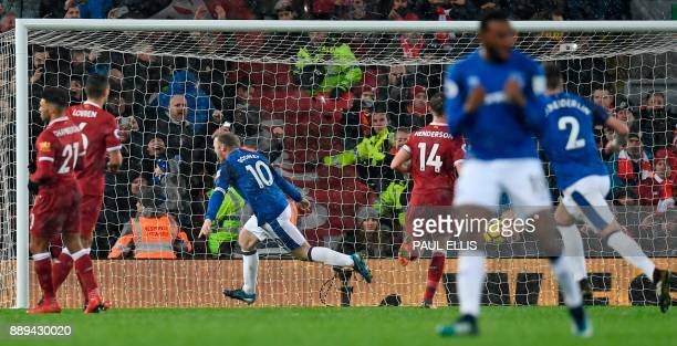 Everton's English striker Wayne Rooney runs away to celebrate after scoring an equalising goal from the penalty spot to make the score 11 during the...