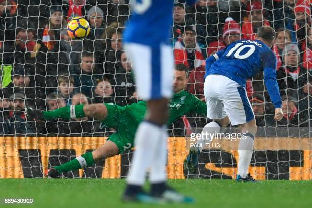 Everton's English striker Wayne Rooney scores an equalising goal from the penalty spot to make the score 11 during the English Premier League...