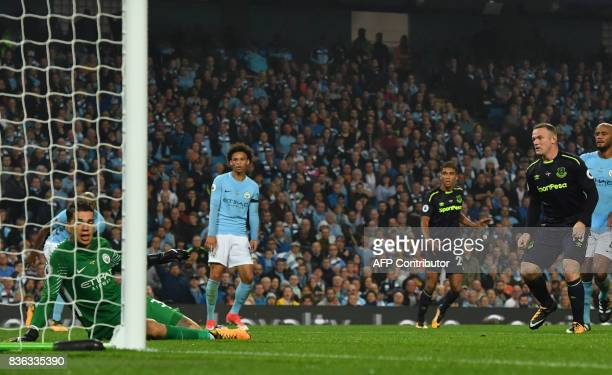 Everton's English striker Wayne Rooney scores his team's first goal past Manchester City's Brazilian goalkeeper Ederson during the English Premier...