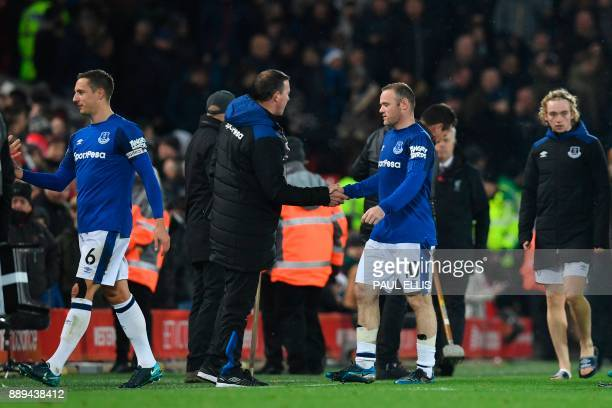 Everton's English striker Wayne Rooney shakes hands with a member of Everton staff at the end of the English Premier League football match between...