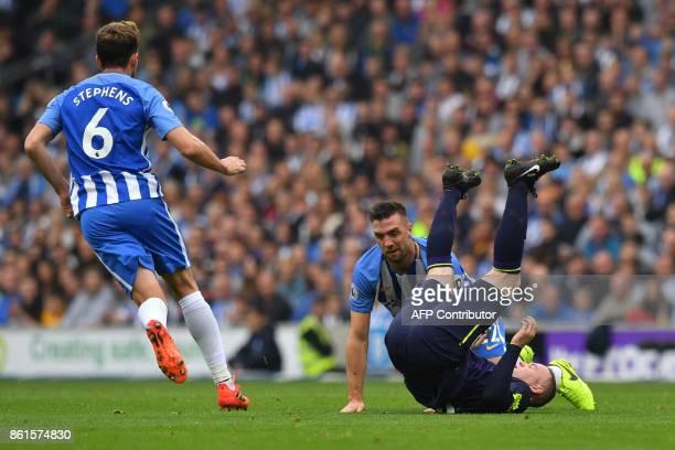 Everton's English striker Wayne Rooney takes a tumble with Brighton Irish defender Shane Duffy as Brighton's English midfielder Dale Stephens looks...