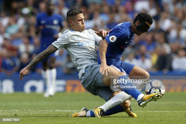 Everton's Germanborn Bosnian midfielder Muhamed Besic tackles Repsol Honda Team's Spanish rider Dani Pedrosa during the English Premier League...