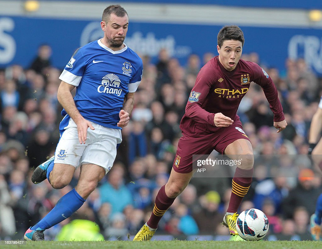 Everton's Irish footballer Darron Gibson (L) vies for the ball against Manchester City's French footballer Samir Nasri during their English Premier League football match between Everton and Manchester City at the Goodison Park Stadium in Liverpool, north west England, on March 16, 2013. USE. No use with unauthorized audio, video, data, fixture lists, club/league logos or 'live' services. Online in-match use limited to 45 images, no video emulation. No use in betting, games or single club/league/player publications.