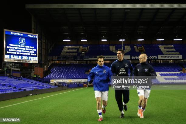 Everton's Leighton Baines Joel Robles and Steven Naismith warm down after learning their Barclays Premier League match has been abandoned at Goodison...
