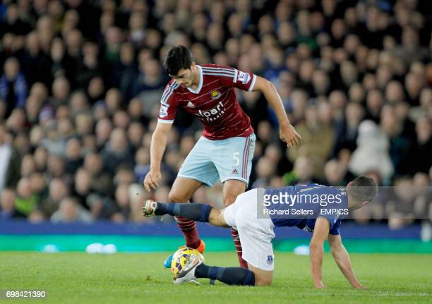 Everton's Leon Osman and West Ham United's James Tomkins challenge for the ball
