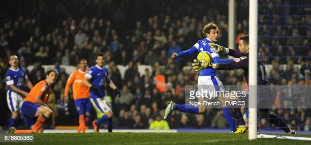 Everton's Leon Osman watches as his header beats Oldham Athletic's goalkeeper Dean Bouzanis