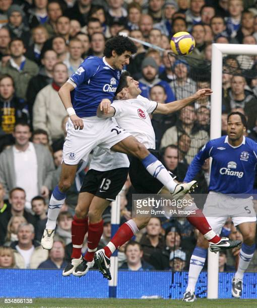 Everton's Marouane Fellaini and Fulham's Aaron Hughes battle for the ball