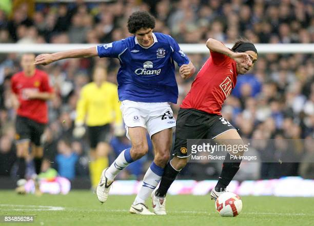 Everton's Marouane Fellaini and Manchester United's Carlos Tevez battle for the ball