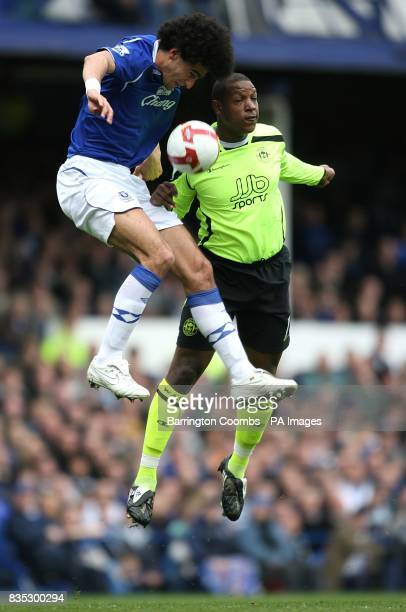 Everton's Marouane Fellaini and Wigan Athletic's Titus Bramble battle for a ball in the air