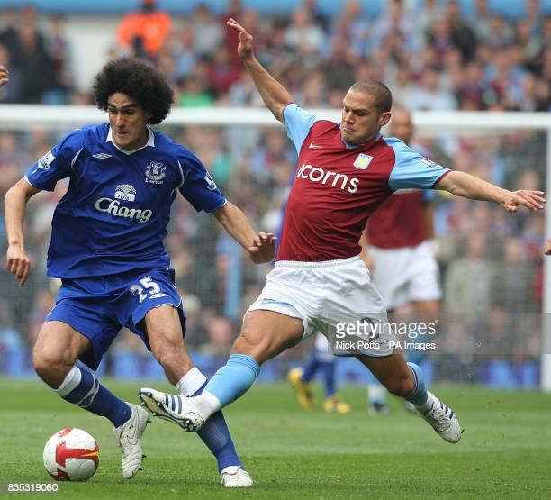 Everton's Marouane Fellaini is challenged by Aston Villa's Luke Young