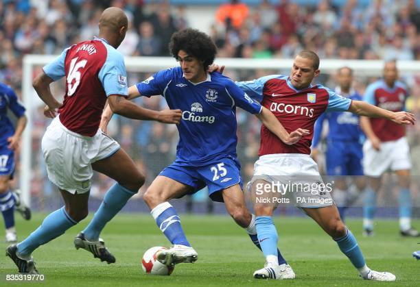 Everton's Marouane Fellaini is challenged by Aston Villa's Zat Knight and Luke Young