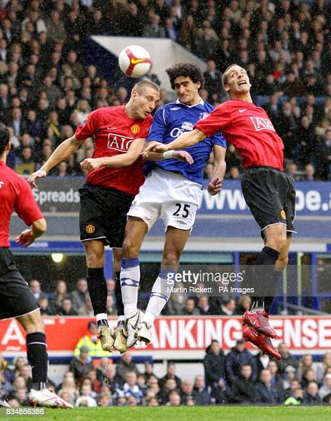 Everton's Marouane Fellaini is challenged by Manchester United's Nemanja Vidic and Rio Ferdinand