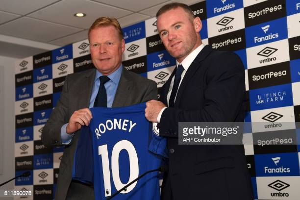Everton's new signing English striker Wayne Rooney poses for a photograph with his new club shirt held by Everton's Dutch manager Ronald Koeman...