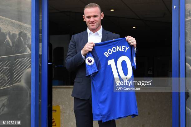 Everton's new signing English striker Wayne Rooney poses for a photograph with his club shirt after giving a press conference at Goodison Park in...