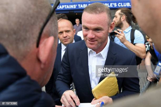 Everton's new signing English striker Wayne Rooney signs autographs for supporters after giving a press conference at Goodison Park in Liverpool on...