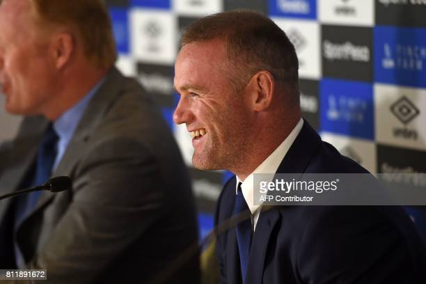 Everton's new signing English striker Wayne Rooney smiles during a press conference at Goodison Park in Liverpool on July 10 following his move to...