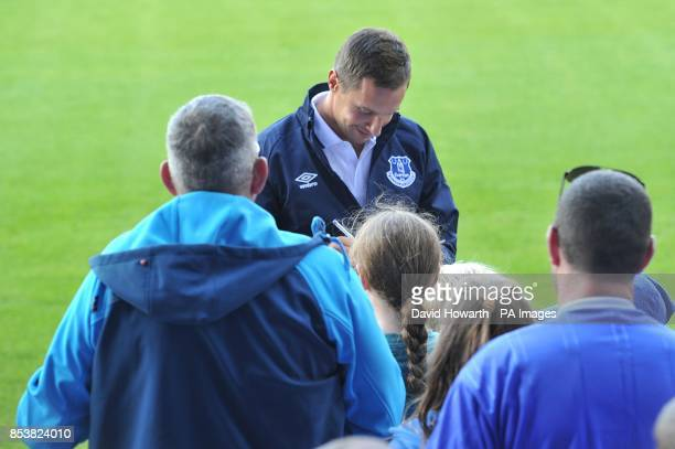Everton's Phil Jagielka signs autographs for fans before the match