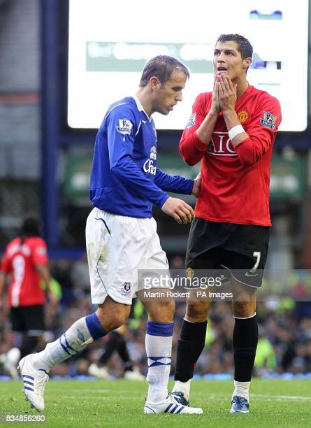 Everton's Phil Neville walks by Manchester United's Cristiano Ronaldo who stands dejected after missing a shot on goal