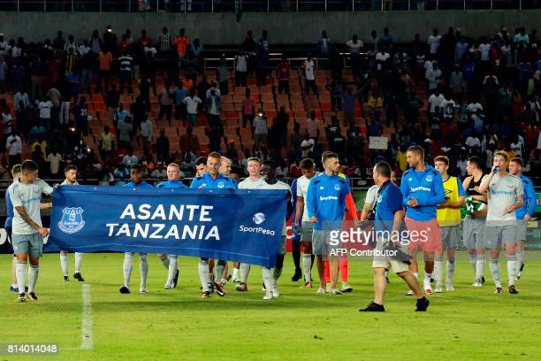 Everton's players hold a banner reading 'Thanks Tanzania' after winning a friendly football match between Everton and Kenya's Gor Mahia at the...