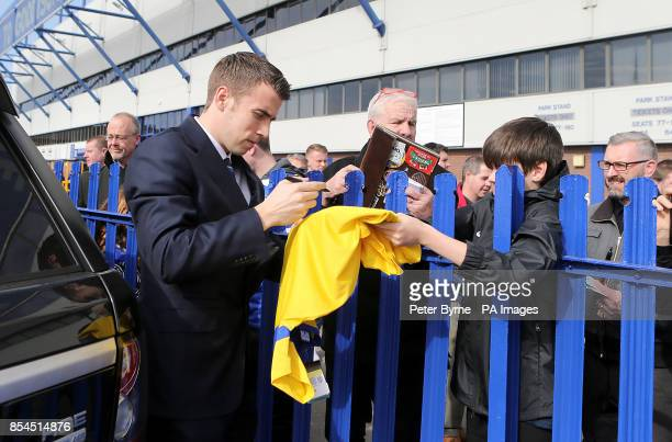 Everton's Seamus Coleman signs autographs for fans outside Goodison Park before the game