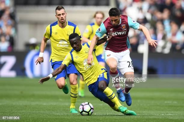 Everton's Senegalese midfielder Idrissa Gueye tackles West Ham United's Argentinian striker Jonathan Calleri during the English Premier League...