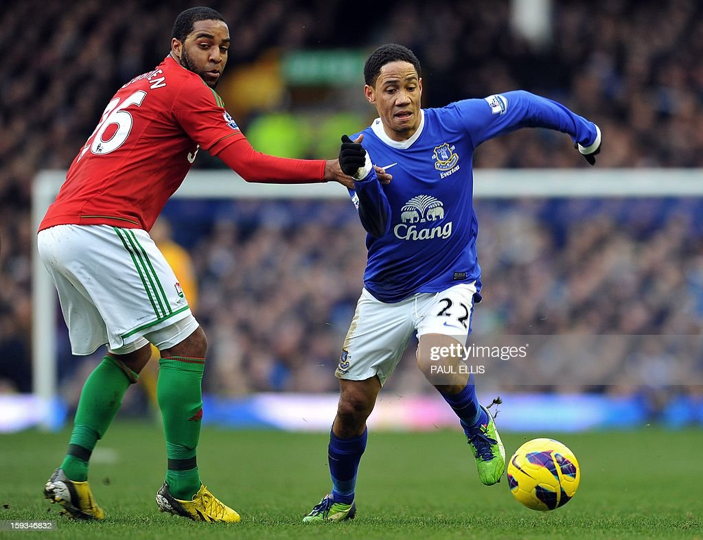 """Everton's South African midfielder Steven Pienaar (R) is challenged by Swansea City's Dutch midfielder Kemy Agustien during the English Premier League football match between Everton and Swansea City at Goodison Park in Liverpool on January 12, 2013. AFP PHOTO/Paul ELLIS- RESTRICTED TO EDITORIAL USE. No use with unauthorized audio, video, data, fixture lists, club/league logos or """"live"""" services. Online in-match use limited to 45 images, no video emulation. No use in betting, games or single club/league/player publications."""
