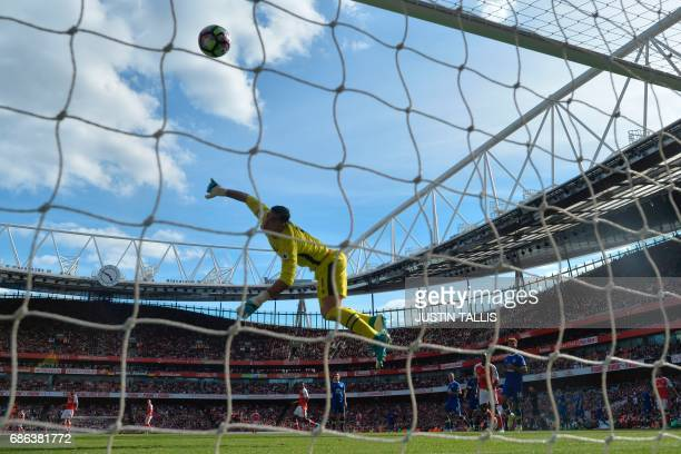 Everton's Spanish goalkeeper Joel Robles dives in vain as Arsenal's Welsh midfielder Aaron Ramsey scores their third goal during the English Premier...