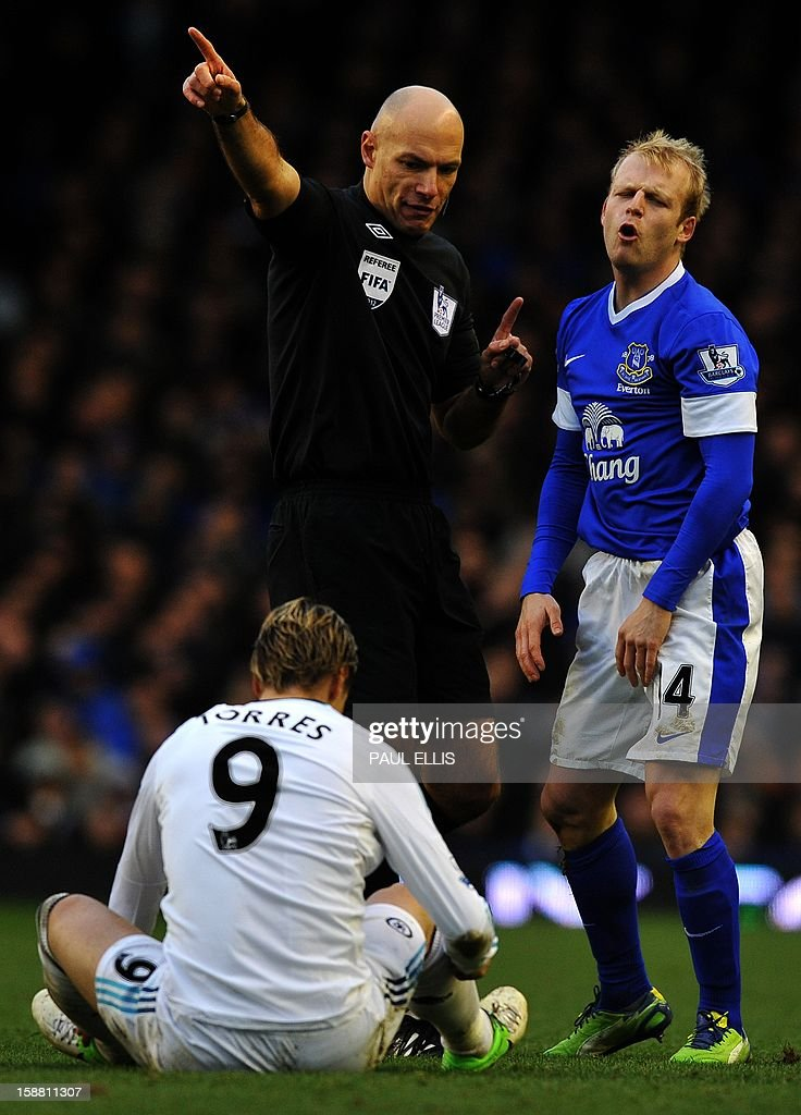 Everton's Steven Naismith (R) reacts as referee Howard Webb (C) indicates a free kick for Chelsea's Fernando Torres during the English Premier League football match between Everton and Chelsea at Goodison Park in Liverpool, England on December 30, 2012. Chelsea won 2-1. AFP PHOTO/Paul Ellis - RESTRICTED