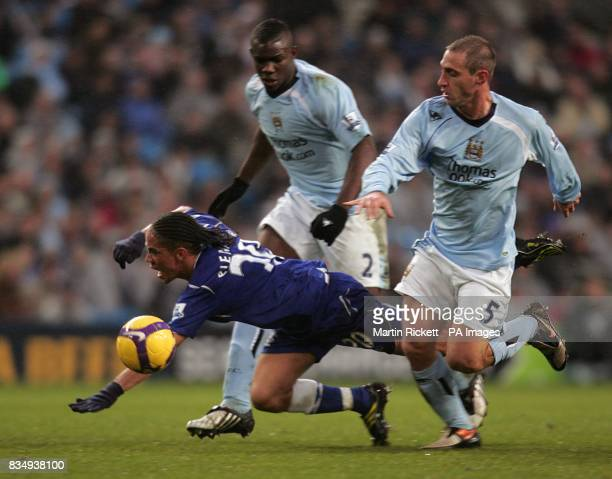Everton's Steven Pienaar falls after battling with Manchester City's Micah Richards and Pablo Zabaleta right for the ball