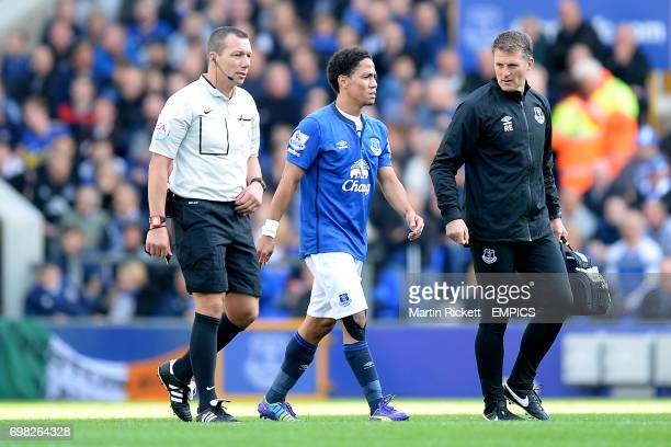 Everton's Steven Pienaar leaves the pitch with an injury with head of performance Richard Evans and referee Kevin Friend