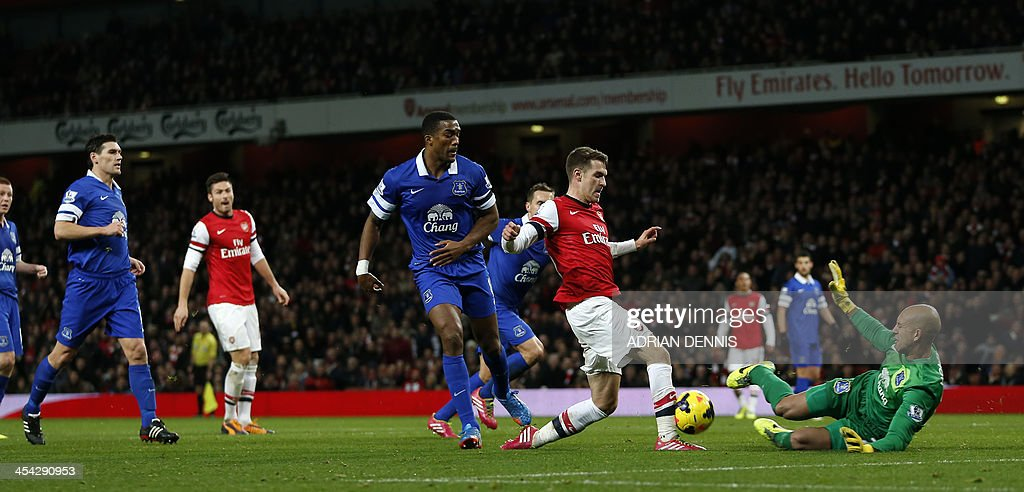 Everton's US goalkeeper Tim Howard (R) makes a save from Arsenal's Welsh midfielder Aaron Ramsey (2nd R) during the English Premier League football match between Arsenal and Everton at The Emirates Stadium in north London on December 8, 2013.
