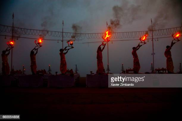 Every morning just before sunrise priests celebrate Aarti Puja ceremony to the God of Fire and mother River Ganges using large oil lamps while...