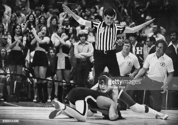 Everybody Gets Into The Act The referee signals Battle Mountain High School coaches watch intently and the school's cheerleaders offer encouragement...