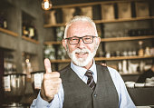 Everything is ok. Small business. Portrait of senior businessman with thumb up looking at the camera.